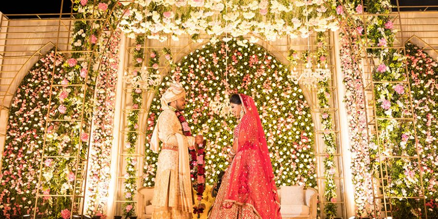 This couple's plush wedding reflected the vibrancy of Gujrati culture with its tall gold archways, pink blooms, and vintage chandeliers