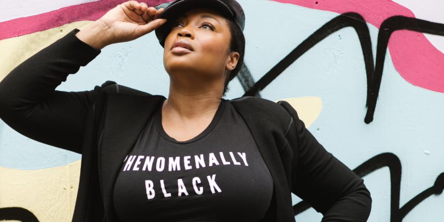 "Plus Size Black Model Posing While Wearing Black T-shirt That Says ""Phenomenally Black"" Against Colored BackDrop"